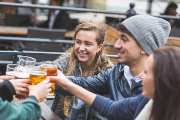 Group of friends enjoying a beer at pub in London, toasting and laughing. Close up on two girls and a boy.